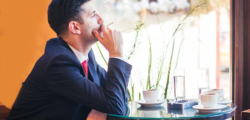 Homme dans un café fumant une cigarette