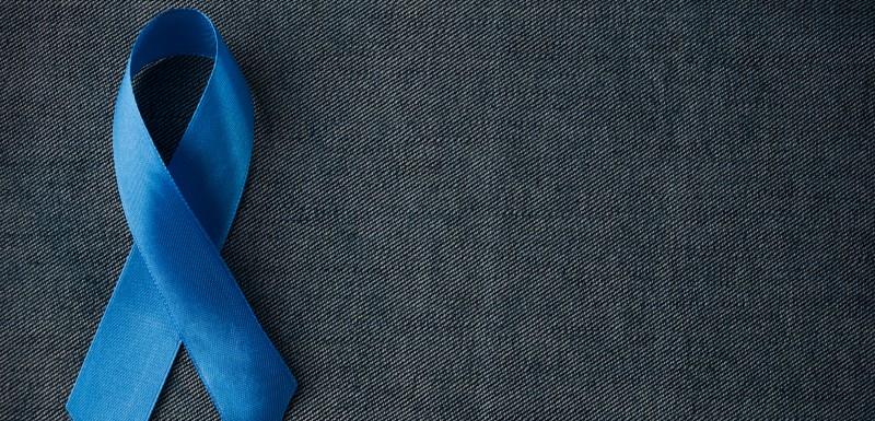 Ruban de tissu bleu signifiant le cancer de la prostate sur fond gris foncé